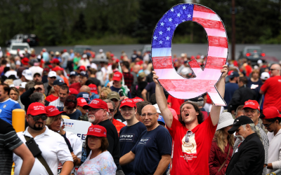 "David Reinert holds up a large ""Q"" sign, representing QAnon, a conspiracy theory group, while waiting in line to see President Donald Trump at a rally in Wilkes-Barre, Pa., Aug. 2, 2018. (Rick Loomis/Getty Images via JTA)"