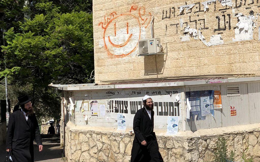 "Ultra-Orthodox people walk past a ""modesty sign"" in Beit Shemesh. (Sam Sokol)"