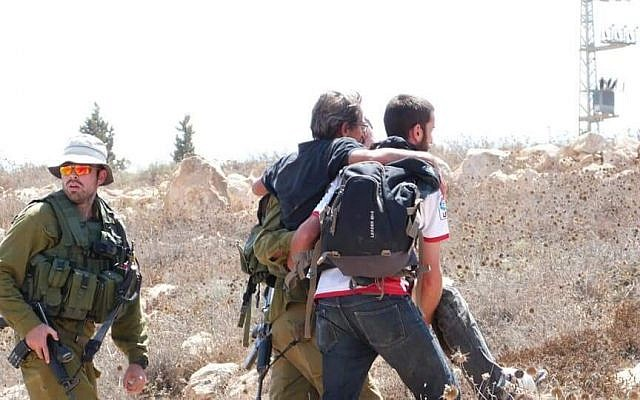 An injured left-wing activist being escorted by IDF soldiers, near the West Bank settlement of Mitzpeh Yair, August 25, 2108. (B'Tselem)