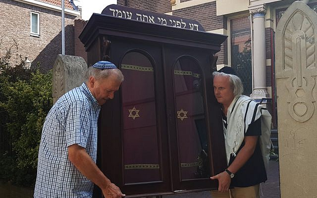 Tom Furstenberg, right, and a fellow congregant carrying the Torah ark out of the Great Synagogue of Deventer, July 30, 2018. (Cnaan Liphshiz)