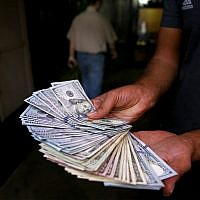 An illegal street money changer poses with his US banknotes in downtown Tehran, Iran, August 7, 2018. (AP Photo/Ebrahim Noroozi)