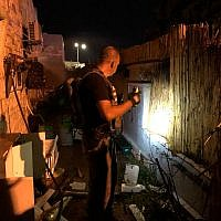 A police sapper searches the yard of a house the southern Israeli town of Sderot that was hit by a rocket attack from the Gaza Strip on August 8, 2018. (Israel Police)