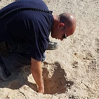 A police officer inspects a crater caused by a rocket fired from the Gaza Strip that struck an open field north of the city of Beersheba on August 9, 2018. (Israel Police)
