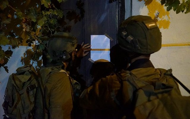 Israeli soldiers post a demolition notice on the home of a Palestinian terrorist from the West Bank village of Kobar who stabbed to death an Israeli man last month, on August 13, 2018. (Israel Defense Forces)