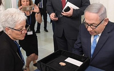 "Prime Minister Benjamin Netanyahu and Amanda Weiss, director of the Bible Lands Museum in Jerusalem, with a 2,600-year-old clay tablet bearing the name ""Benayahu ben Netanyahu"" which is being loaned to the Prime Minister's Office for the coming year, August 21, 2018 (GPO)"