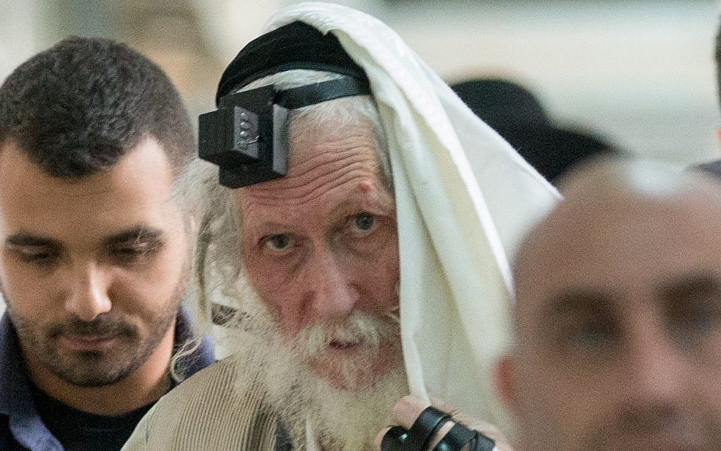 Rabbi Eliezer Berland shrouds himself with his talit (prayer shawl) at the Magistrates Court in Jerusalem, as he is put on trial for sexual assault charges, November 17, 2016. (Yonatan Sindel/ Flash90)
