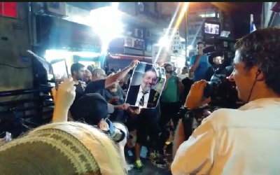 Protesters in southern Tel Aviv burn a photo of Interior Minister Aryeh Deri to protest the continued presence of tens of thousands of African asylum seekers in their impoverished neighborhoods, August 30, 2018 (Hadashot screen capture)