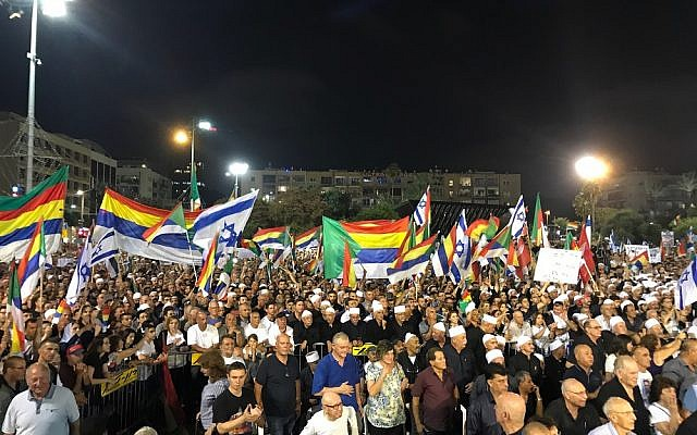 Protesters wave Israeli and Druze flags at a demonstration in Tel Aviv against the nation-state law, on August 4, 2018. (Luke Tress / Times of Israel staff)