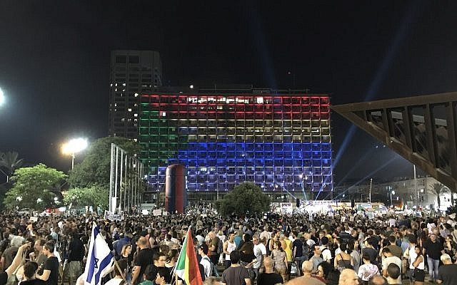 Protesters wave Israeli and Druze flags at Rabin Square during a demonstration in Tel Aviv against the nation-state law, on August 4, 2018. (Luke Tress / Times of Israel staff)