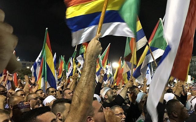 Protesters wave Israeli and Druze flags at a demonstration against the nation-state law, in Tel Aviv's Rabin Square on August 4, 2018. (Luke Tress / Times of Israel staff)