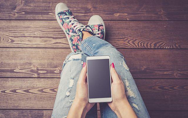 A girl holding a phone (illustrative image: iStock/LeszekCzerwonka)
