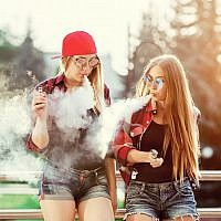 Illustrative image of two women vaping outdoor. (iStock by Getty Images/licsiren)