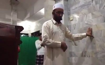 An Imam at a mosque in Bali steadies himself, as a deadly earthquake hits on August 5, 2018. (Screen capture: YouTube)