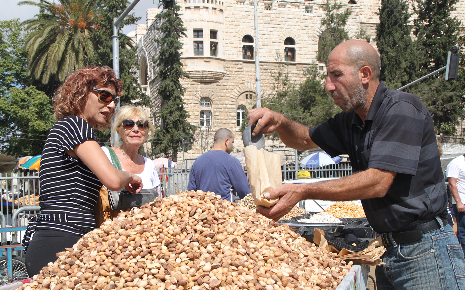 Tourists and residents buy snacks outside the entrance to Damascus Gate. (Shmuel Bar-Am)