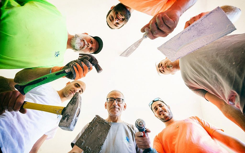 A construction team from Tenufa Bakehila - Building Hope, a nonprofit organization founded to help low-income families fix and renovate their homes (Courtesy Jordan Polevoy)