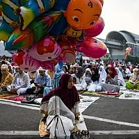 An Indonesian woman sells balloons as other gather outside a mosque before Eid al-Adha prayers in Palembang on August 22, 2018. (AFP PHOTO / MOHD RASFAN)