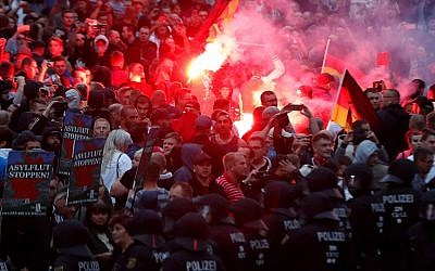 Far-right demonstrators light flares in Chemnitz, eastern Germany, on September 7, 2018, after a 35-year-old German was stabbed to death in August 2018. (AFP/Odd Andersen)