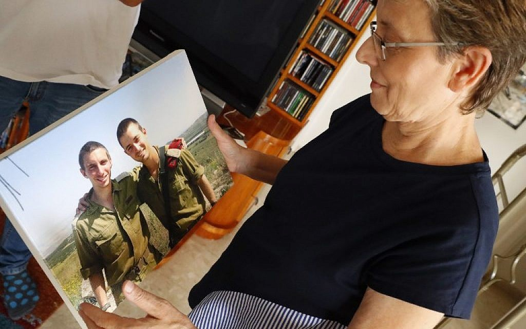 Leah Goldin (R), the mother of Israeli soldier Lieutenant Hadar Goldin (L), holds up a picture of her son as she speaks during an interview at their family home in the central Israeli city of Kfar Saba on August 29, 2018. (AFP PHOTO / JACK GUEZ)