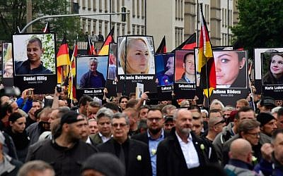 Demonstrators hold up placards showing portraits of victims of refugees during a protest organized by the far-right Alternative for Germany (AfD) party, on September 1, 2018 in Chemnitz, eastern Germany. (AFP PHOTO / John MACDOUGALL)