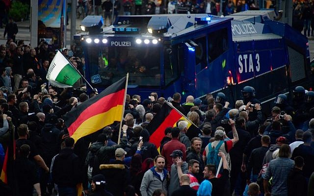 """Demonstrators crowd around a water cannon of the police during a protest organised by the right-wing populist """"Pro Chemnitz"""" movement, the far-right Alternative for Germany (AfD) party and the anti-Islam Pegida movement, on September 1, 2018 in Chemnitz, eastern Germany. (AFP / John MACDOUGALL)"""