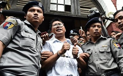 Myanmar journalist Wa Lone (C) is escorted by police after being sentenced by a court to jail in Yangon on September 3, 2018. (AFP PHOTO / Ye Aung THU)