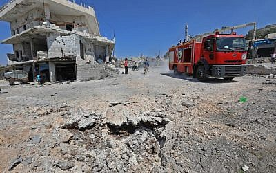 A picture taken on September 4, 2018 shows a fire engine drive through a damaged road after a reported Russian airstrike in the rebel-hold town of Muhambal, about 30 kilometers southwest of the city of Idlib. (AFP/Omar Haj Kadour)