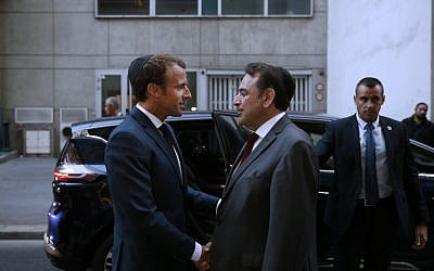President of the Central Jewish Consistory of Paris Joel Mergui (C) greets French President Emmanuel Macron (L) upon his arrival to attend a ceremony to mark the Jewish New Year - Rosh Hashanah - at The Great Synagogue in Paris on September 4, 2018. (AFP PHOTO / POOL / YOAN VALAT)