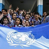 Palestinian school children chant slogans and raise the victory gesture over a UN flag during a protest at a United Nations Relief and Works Agency (UNRWA) school, financed by US aid, in the Arroub refugee camp near Hebron in the West Bank on September 5, 2018. (AFP PHOTO / HAZEM BADER)