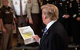 """US President Donald Trump reads from an article praising his administration as he answers a journalist during a meeting with sheriffs at the White House in Washington, DC, on September 5, 2018. Trump was responding to an anonymous """"senior official"""" who wrote an op-ed article entitled """"I Am Part of the Resistance Inside the Trump Administration"""" in The New York Times on September 5. (AFP PHOTO / NICHOLAS KAMM)"""