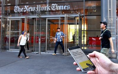 """A smartphone displaying a New York Times opinion piece titled """"I Am Part of the Resistance Inside the Trump Administration"""" is held up in this illustration in front of the New York Times building on September 6, 2018 in New York. (AFP/ ANGELA WEISS)"""