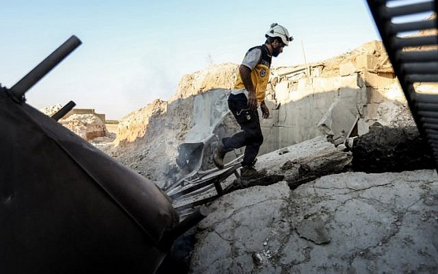 "This picture taken on September 6, 2018 shows a member of the Syrian Civil Defence, also known as the ""White Helmets"", walking through the wreckage of their center which was destroyed by government forces' bombardment in the town of al-Tamana on the southern edges of the rebel-held Idlib province. (AFP OMAR HAJ KADOUR)"
