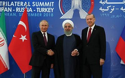 A handout picture taken and released on September 7, 2018, by the Turkish Presidential Press service shows Turkish President Recep Tayyip Erdogan (R) , Iranian President Hassan Rouhani (C) and Russian President Vladimir Putin (L) joining hands  during a trilateral summit in Tehran. (AFP/Turkish Presidency Press Office)