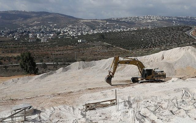 A crane is used at the construction site in the West Bank settlement of Amichai on September 7, 2018. (AFP/Thomas Coex)