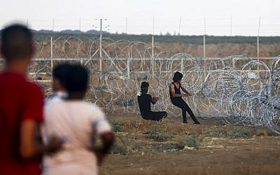 Illustrative. Palestinians pull on a cable tied to a barbed-wire fence as they try to pull down a section of the security fence between the Gaza Strip and Israel, during border clashes east of Gaza City, on September 7, 2018. (AFP/Said Khatib)