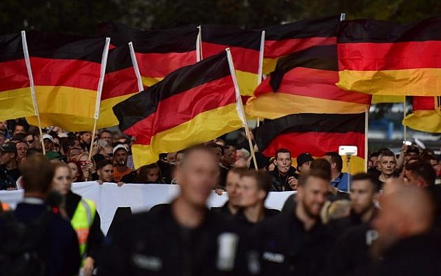 People hold national flags during a march organized by the right-wing populist 'Pro Chemnitz' movement on September 7, 2018 (AFP PHOTO / John MACDOUGALL)