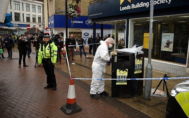 A police forensics officer looks for evidence inside a cordon in Peel Square, following a stabbing incident in the centre of Barnsley, northern England on September 8, 2018. (AFP PHOTO / Oli SCARFF)