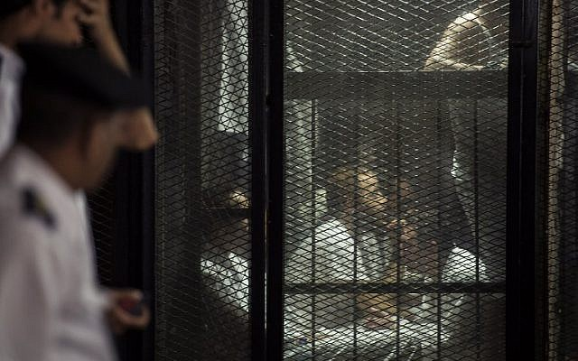 This picture shows detainees inside the soundproof glass dock of the courtroom during the trial of 700 defendants including Egyptian photojournalist Mahmoud Abu Zeid, widely known as Shawkan, in the capital Cairo, on September 8, 2018. ( AFP PHOTO / Mohamed el-Shahed)