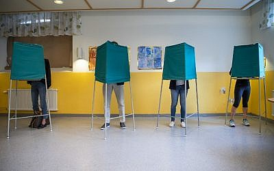 People stand on booths at a polling station during the Swedish general elections in Stockholm on September 9, 2018. (AFP Photo/Jonathan Nackstrand)