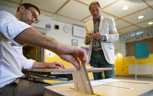 An election official casts a voter's ballot at a polling station during the Swedish general elections in Stockholm on September 9, 2018. (AFP Photo/Jonathan Nackstrand)