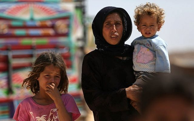 A woman who fled her village in Syria's Idlib province carries a child at a camp in Kafr Lusin near the border with Turkey in the northern part of the province on September 9, 2018. (AFP PHOTO / Aref Tammawi)