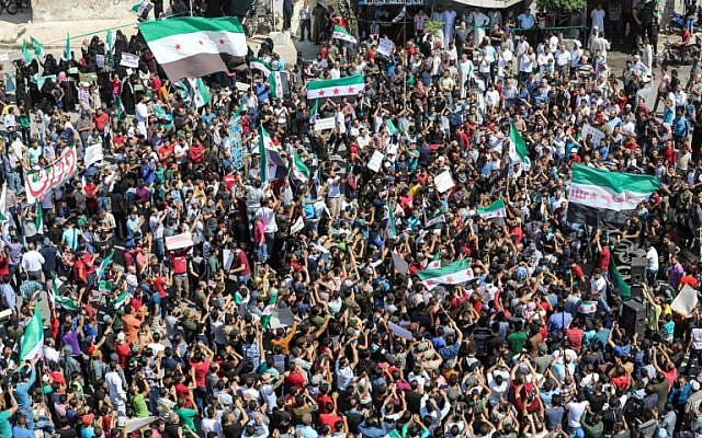 Syrians from the rebel-held northern city of Idlib and its surrounding towns wave opposition flags and chant slogans as they gather for an anti-government demonstration in Idlib on September 14, 2018. (AFP Photo/Omar Haj Kadour)