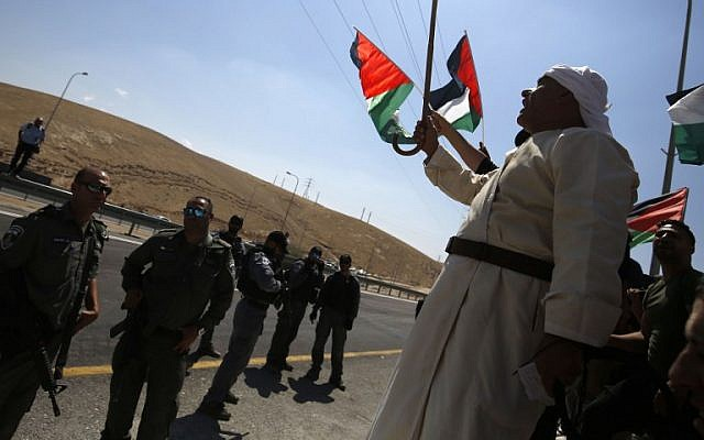 Palestinian protesters wave national flags in front of Israeli troops during a protest against Israel's plan to demolish the Palestinian Bedouin village of Khan al-Ahmar, in the occupied West Bank September 14, 2018. (AFP PHOTO / ABBAS MOMANI)