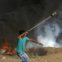 Illustrative: A Palestinian protester uses a slingshot to throw stone toward Israeli forces firing tear gas during a demonstration along the border fence east of Gaza City on September 14, 2018. (AFP/Said Khatib)