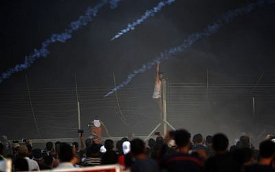 A Palestinian man climbs a fence as tear gas canisters fired by Israeli forces land through black smoke of burning tires during a riot along the security fence east of Gaza City on September 14, 2018. (Said Khatib/AFP PHOTO)