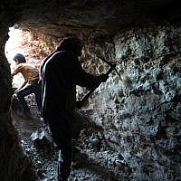 A man uses a pickaxe to dig a cave in the Syrian village of Kafr Ain in the southern countryside of the rebel-held Idlib province on September 15, 2018. (AFP /OMAR HAJ KADOUR)