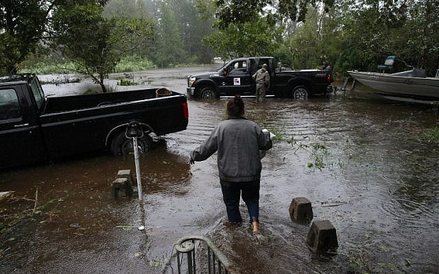 A resident walks from her flooded house towards the crew of the Cajun Navy in Lumberton, North Carolina, on September 15, 2018 in the wake of Hurricane Florence.  (AFP /Alex EDELMAN)