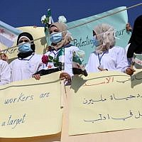 Syrian health sector workers hold banners during a rally in the village of Atmeh in the northern Idlib province, demanding that hospitals be protected in the case of an upcoming  offensive, on September 16, 2018 (AFP PHOTO / OMAR HAJ KADOUR)