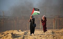 A Palestinian woman carries her national flag during a  protest for lifting the Israeli blockade on Gaza on a beach in Beit Lahia near the maritime border with Israel, on September 17, 2018. (AFP/Said Khatib)