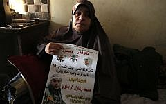 The mother of 24-year-old Palestinian Muhammad Zaghloul Khatib sits at the family's home in the West Bank village of Bayt Rima, north of Ramallah, on September 18, 2018. (AFP Photo/Abbas Momani)