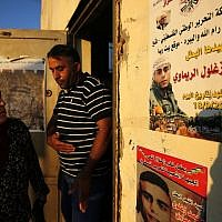 Neighbours of 24-year-old Palestinian Muhammad Zaghloul Khatib look at his poster in the West Bank village of Bayt Rima, north of Ramallah, on September 18, 2018. (AFP Photo/Abbas Momani)